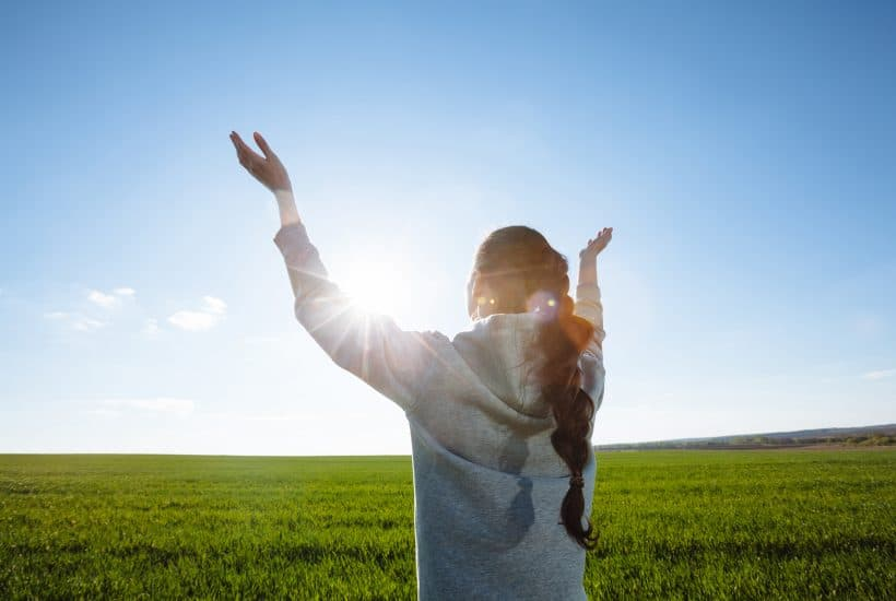 A woman raising her hands and praying in a field.