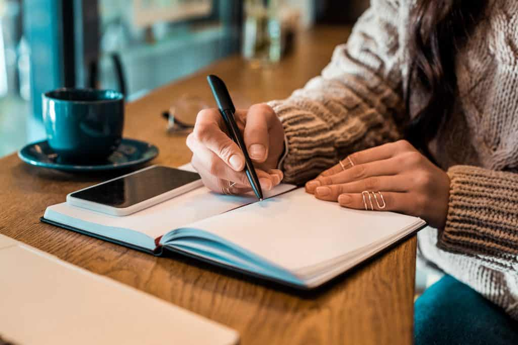 a girl with a cup of coffee writing a gratitude list in her gratitude journal