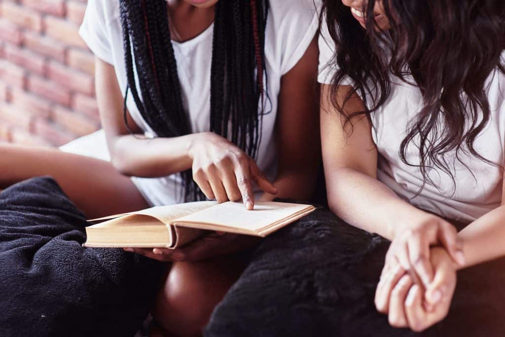 Two woman looking at a book and bible verses about a woman of good character