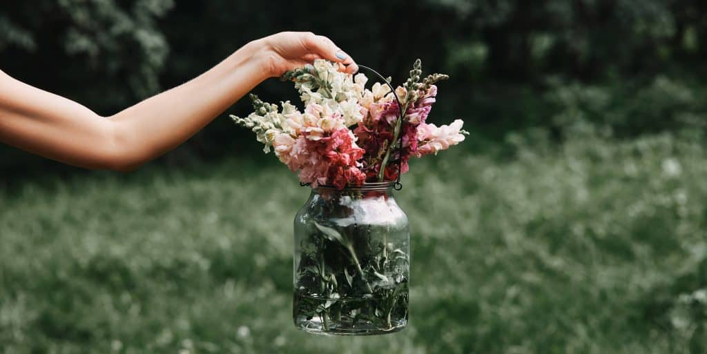 A woman holding a glass jar with colorful flowers