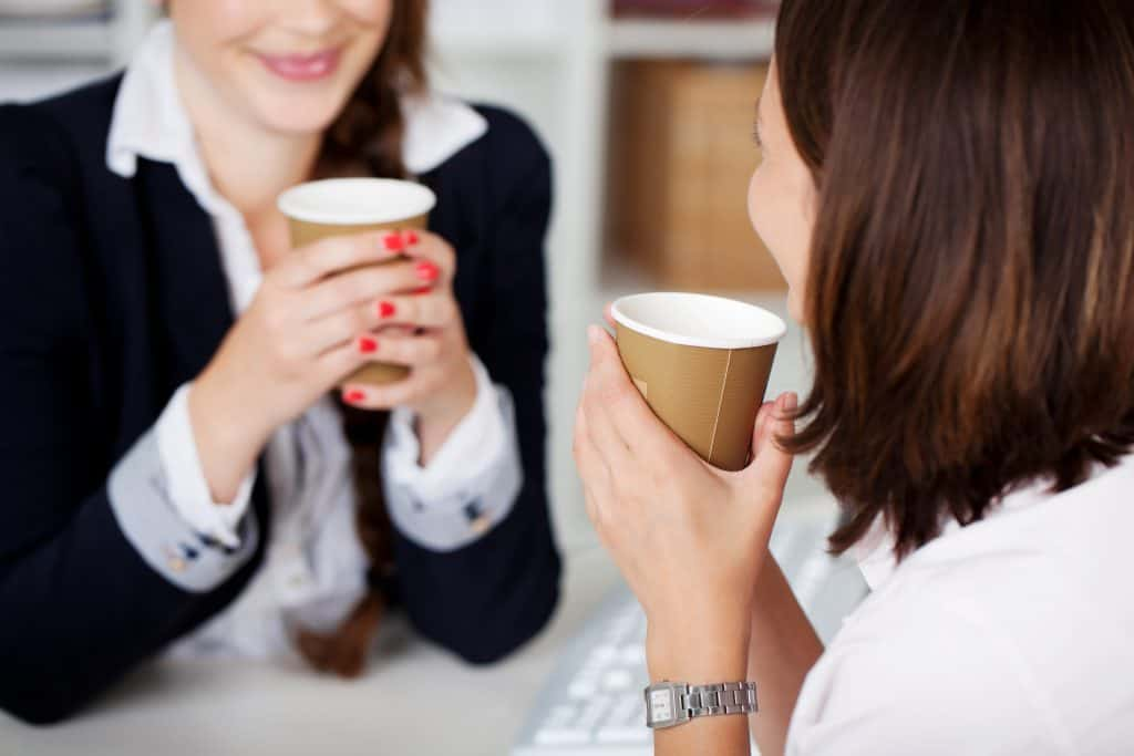 A woman mentoring another woman in the workplace over a cup of coffee