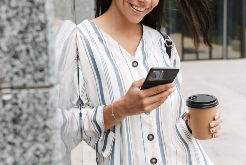 Cropped image of happy young beautiful woman businessman posing outdoors outside walking chatting by mobile phone drinking coffee.