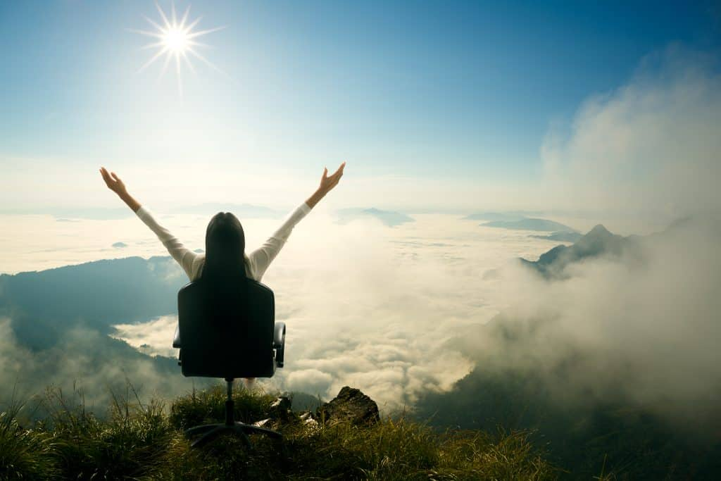 Young woman sits on a chair and open her arms at the top of the mountain, Success in business concept