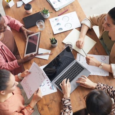 Top view at group of women sitting at wooden meeting table with charts and graphs while discussing business project, having moved on to life after college