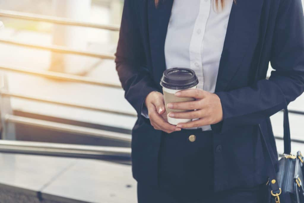 Businesswoman drinking coffee in town using smartphone outside office modern city. She is nervous for the first day of work and wants to make a good impression on her first day.