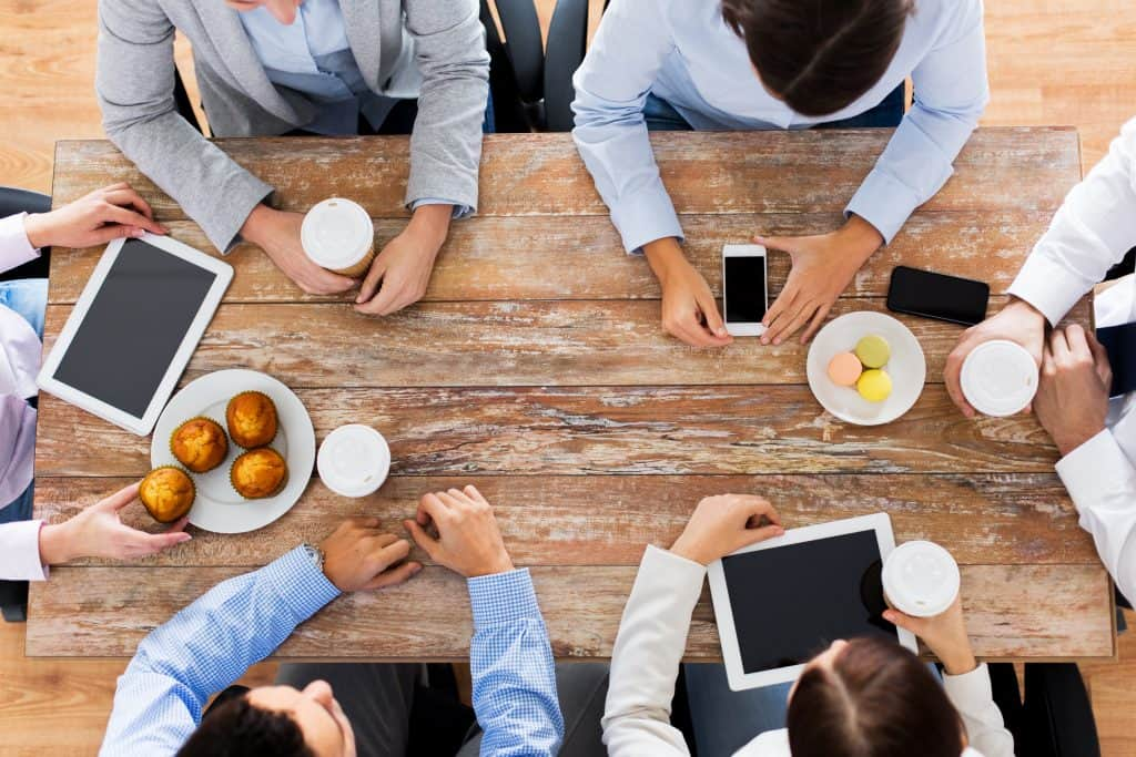 Young professionals gathered around a table networking with each other on coffee break at office