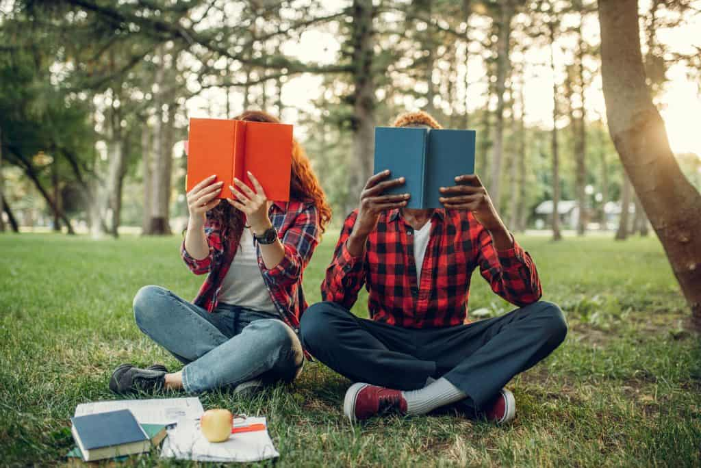 College students sitting on the grass and cover their faces with books on a college campus in the summer.