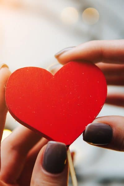 girl holding a red heart in the hands on the background of garlands