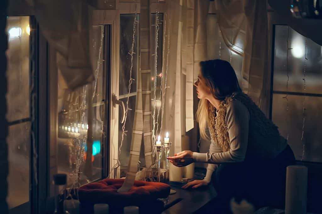 Woman with candles in her apartment; she looks out the window and searches for comfort