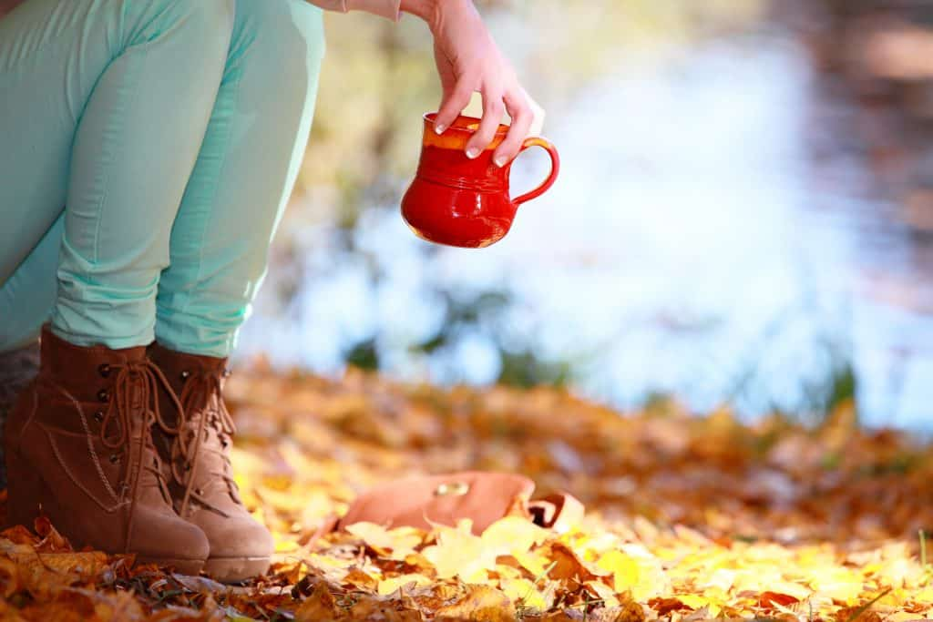 Woman relaxing in the autumn park enjoying hot drink coffee or tea, female hand holding red mug with warm beverage. Yellow leaves background