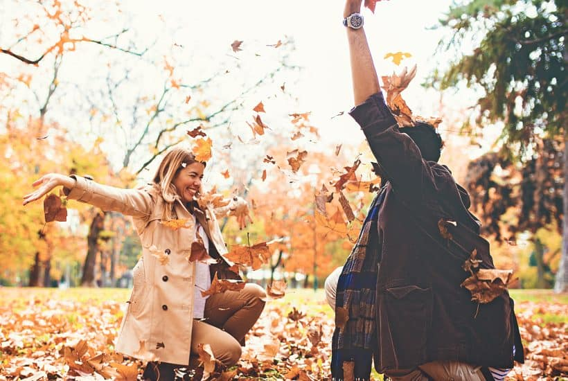 Two people enjoying fall as friends in the park with autumn leaves