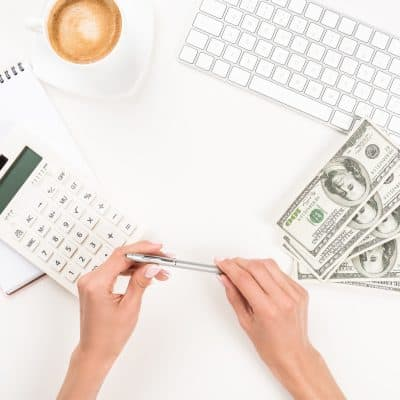young woman sitting at a desk with money about to do budgeting basics