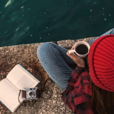 Beautiful woman taking a break from social media and enjoying her day in the lake with a mug of hot coffee
