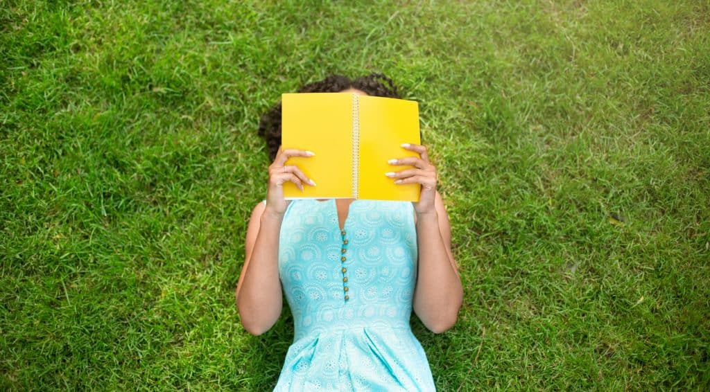 Top view of girl lying on green grass and reading a book of devotionals for Young Professionals.