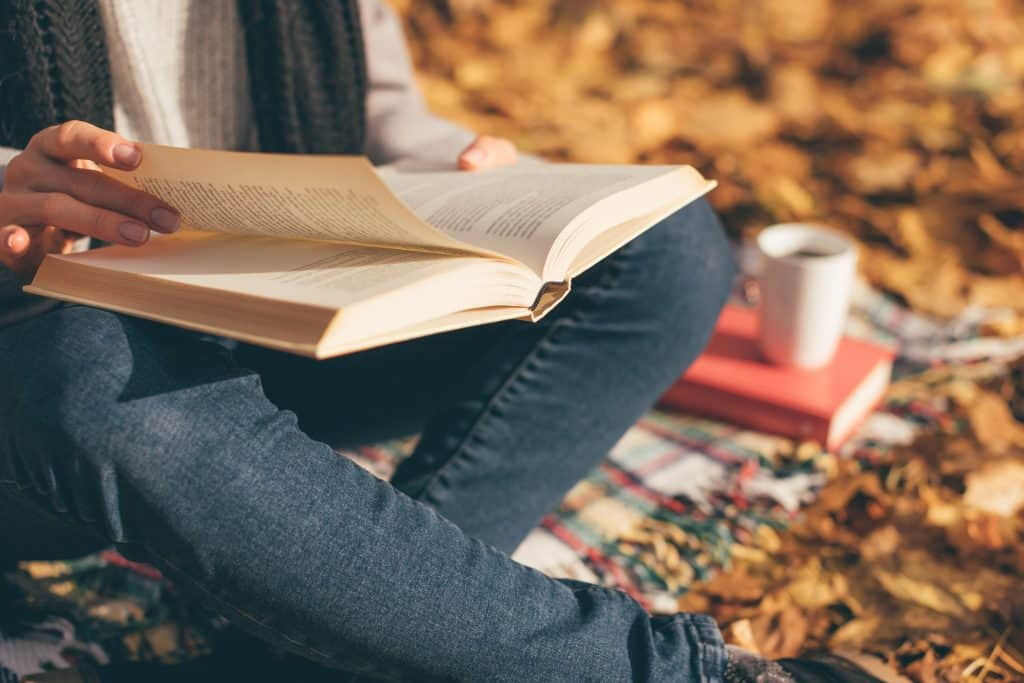 Cropped image of young woman in her 20s sitting on blanket, reading book and drinking coffee or tea in autumn garden