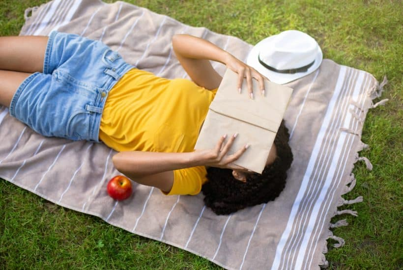 Above view of young woman in her twenties reading a fiction book on picnic blanket outside